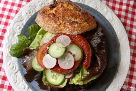 Bratwurstschnecke auf Brotzeitsemmel mit Salat © Liz Collet